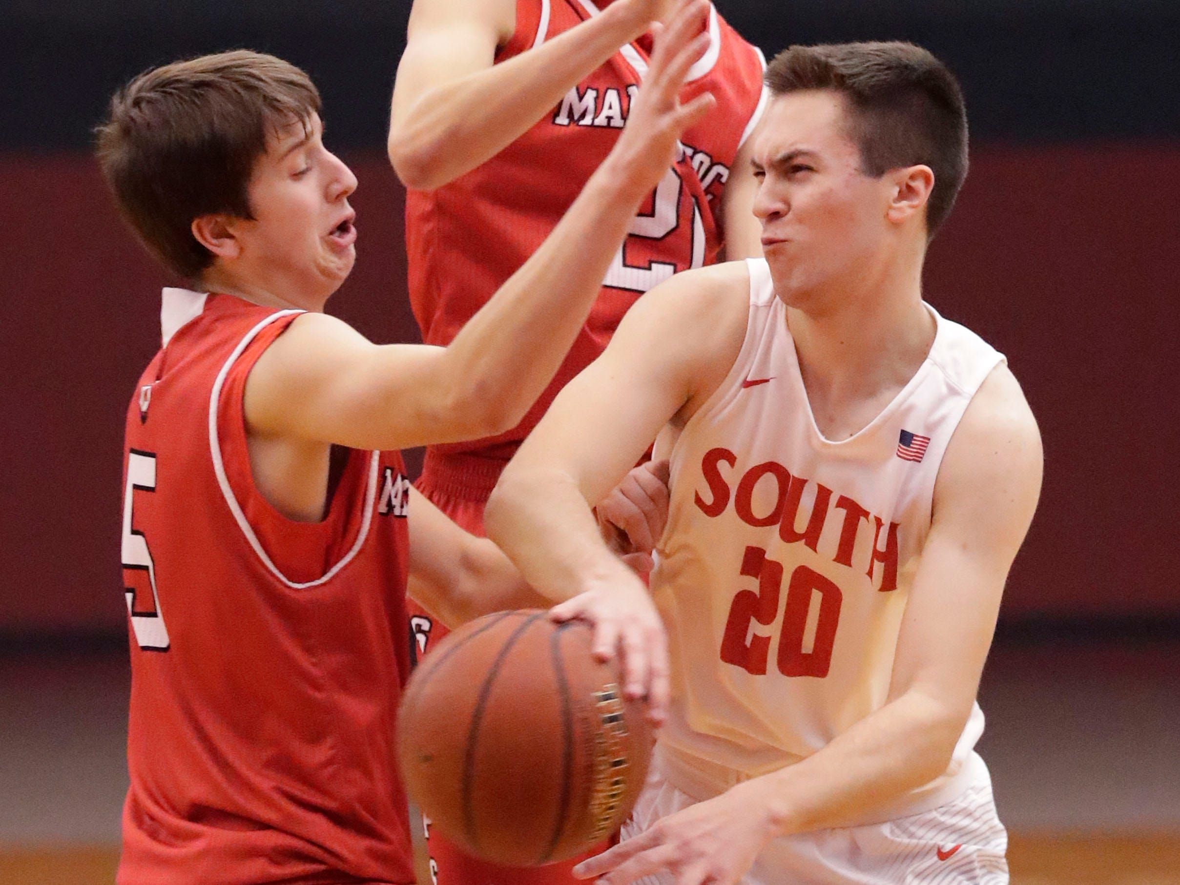 Sheboygan South's Nick Larson (20) passes the ball around two Manitowoc Lincoln players, Tuesday, February 26, 2019, in Sheboygan, Wis.