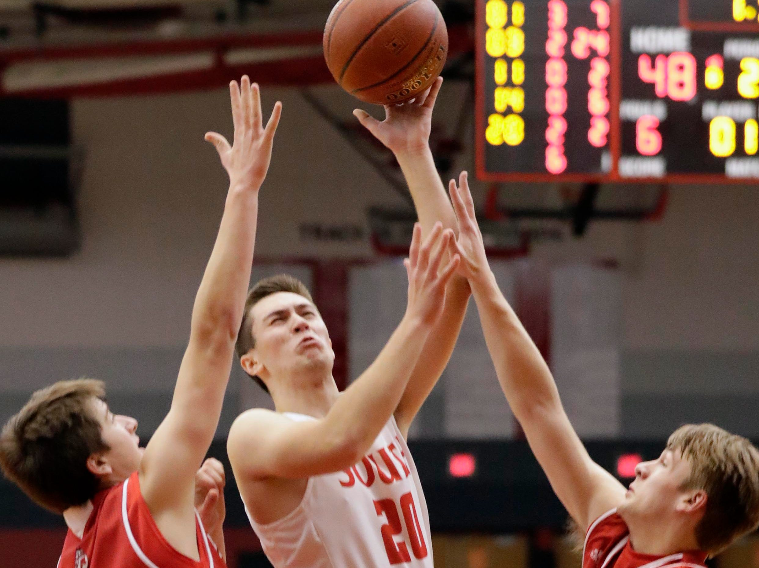 Sheboygan South's Nick Larson (20) grimaces as he shoots the ball while getting pressure from Manitowoc Lincoln players, Tuesday, February 26, 2019, in Sheboygan, Wis.