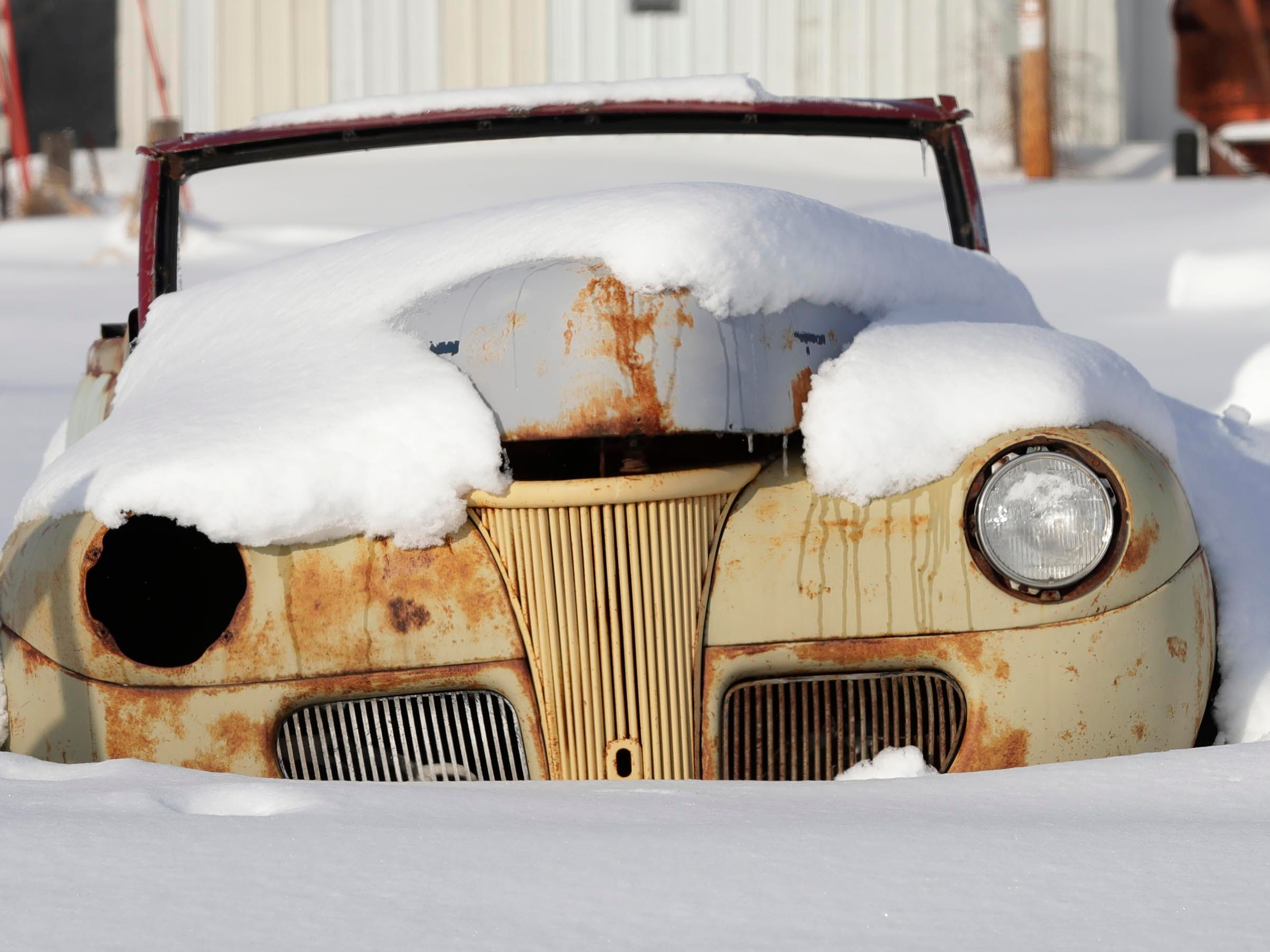 Snow blankets a vintage 1940s car seen along county Highway C near Sheboygan Falls, Wis.