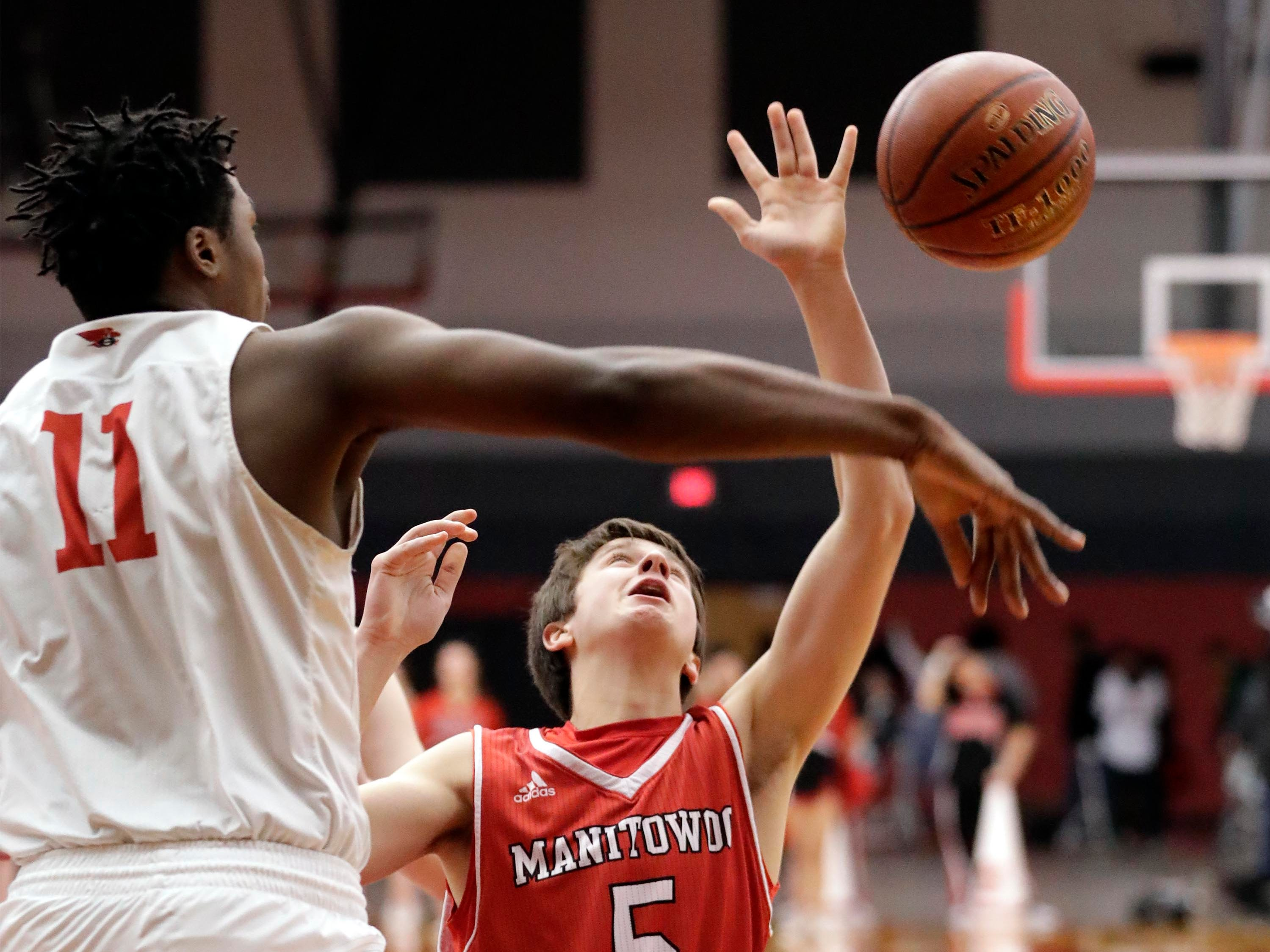 Sheboygan South's Marcell Drone (11) taps the ball away from Manitowoc Lincoln's Josh Hoffman (5), Tuesday, February 26, 2019, in Sheboygan, Wis.