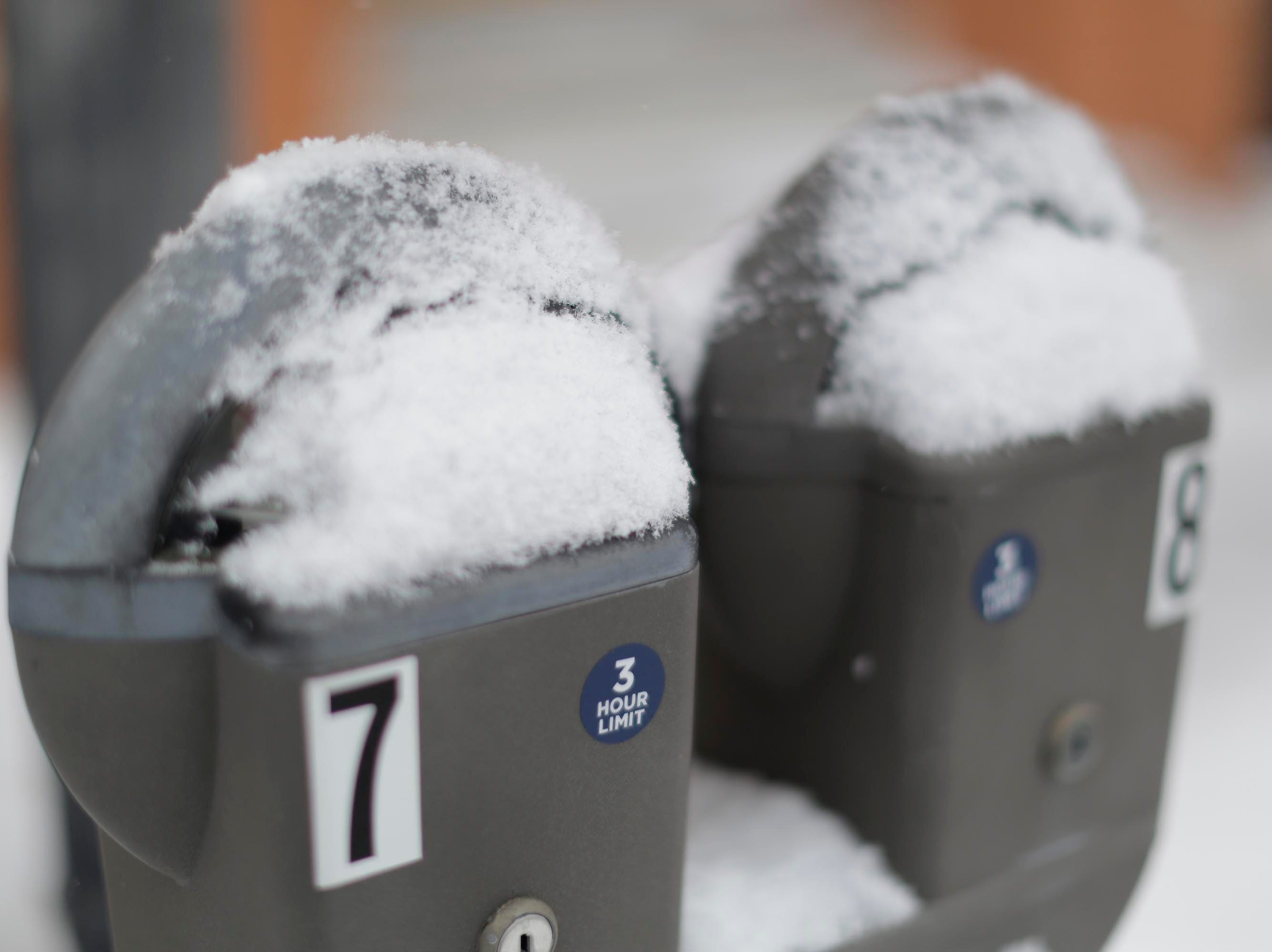 Parking meters in downtown Sheboygan feature a jacket of snow, Wednesday, February 27, 2019, in Sheboygan, Wis.