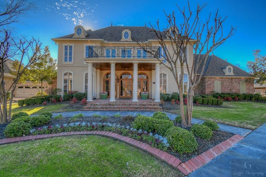 Professional landscaping, neatly trimmed boxwoods and a spacious bricked front porch welcomes guests at 320 Bridgepoint Circle.