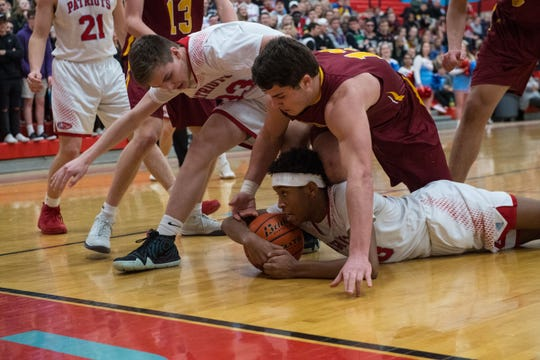 Lincoln and Roosevelt players dive for the ball during a game, Tuesday, Feb. 26, 2019 in Sioux Falls, S.D.