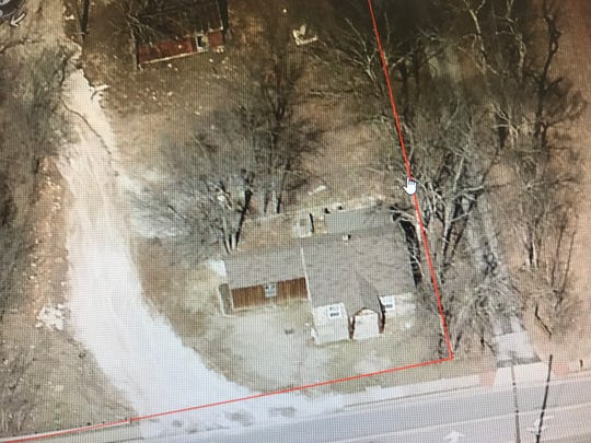 This is an aerial photo of the old stone house at 909 W. Farm Road 182, also known as West Plainview Road. The house is just west of South Campbell Avenue.