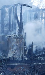 Smoldering remains were all that was left of a double-wide mobile home that caught fire Monday on Pond Gap Lane in Craigsville.