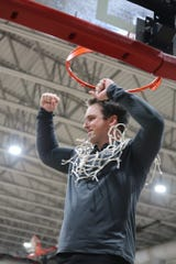 Franklin County boys basketball coach Nathan West cuts down the net after the Seahawks won a regional title and advanced to the Class 1A state tournament for the first time since 2009.