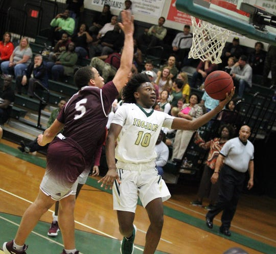 Lincoln's O'rell Brooks drives for a left-handed layup as the Trojans beat Tate 74-41 in a Region 1-8A semifinal on Feb. 26, 2019.