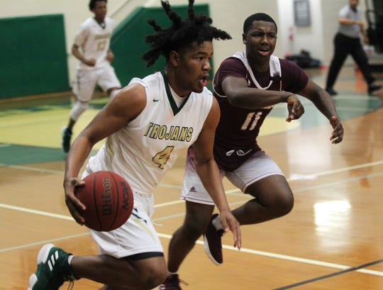 Lincoln's Byron McKnight dribbles up the court as the Trojans beat Tate 74-41 in a Region 1-8A semifinal on Feb. 26, 2019.