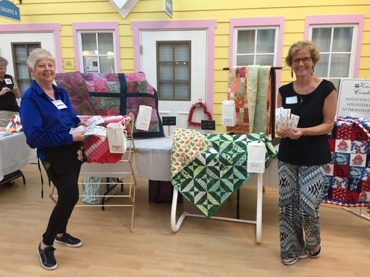 Project Linus members Monica Rodriguez, left, and Melissa King sell raffle tickets at the Kane Center.