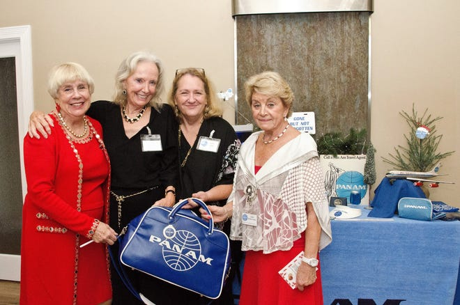 Christmas Gala Event Committee members  Kathy DeMont, left, Laila White, Cathy Liddy and Lissie Carino pause beside a table of Pan Am memorabilia.