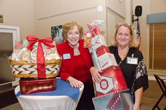 Cathy Liddy, right, presents the Tower of Treats raffle to winner Joan MacLean at the Treasure Coast Chapter of World Wings International Christmas Gala at the Stuart Corinthian Yacht Club.