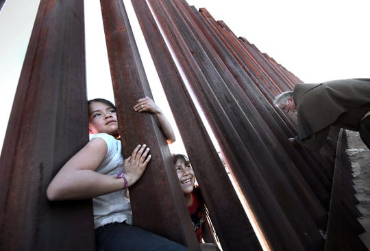 Two girls on the Juarez side of the border fence try to coax Sister Fabiola, who was carrying a huge bag of candy, closer to the fence as Father Miguel Briseño, right, offers a sign of peace to children on the other side of the barrier. Hope Border Institute and the Diocese of El Paso Commission on Migration held a border prayer vigil at the border fence in Anapra Tuesday. Clergy from El Paso, Juarez and New Mexico gathered to pray for migrants and improved immigration policy. Bishop Mark Seitz of El Paso held photos of two children who died in U.S. custody and prayed it would never happen again.