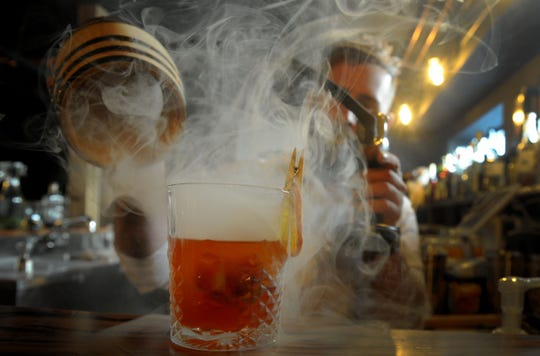 Paul Jones, head bartender at Oak & Iron in Thousand Oaks, makes a Smokey Edward, a blood-orange Old Fashioned that features swirls of pecan-wood smoke. The speakeasy-style craft cocktail lounge opened March 20 and will celebrate its grand opening on April 4.