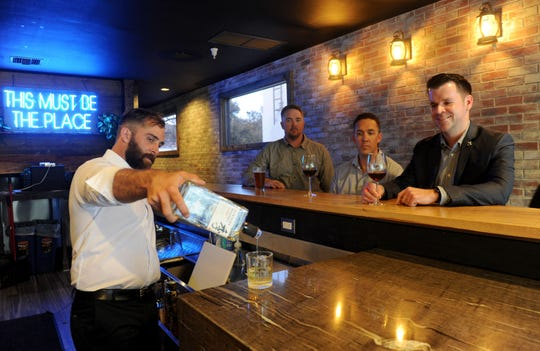 Oak & Iron head bartender Paul Jones, left, pours a drink while co-owners Jared Logan, Jason Logan and Andrew Pletcher look on at the new craft-cocktail bar in Thousand Oaks.