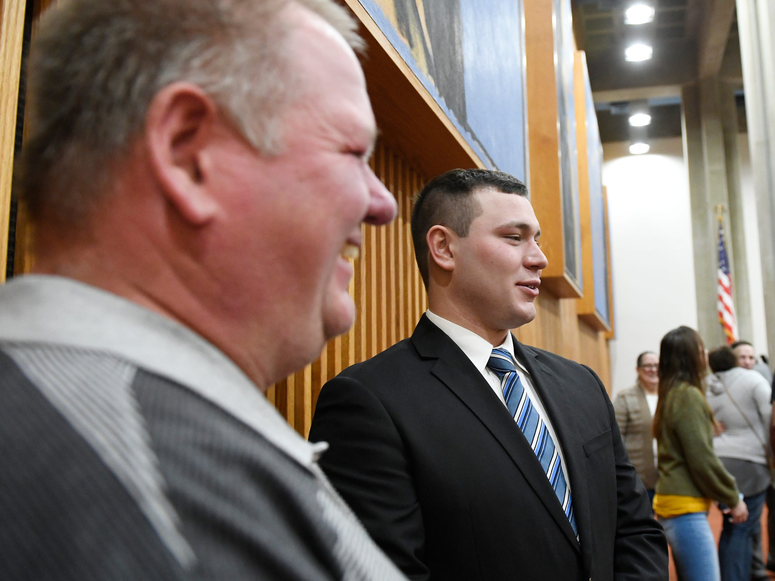 Christopher Yuhas (right) stands next to his father after being sworn in as a police officer at Vineland City Hall on Wednesday, Feb.27, 2019.