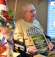 World War II veteran Joe Cuba poses with gifts from the Rider High soccer team Wednesday. Cuba's family requested on social media for him to receive 100 cards for his 100th birthday and he's received approximately 16,000.