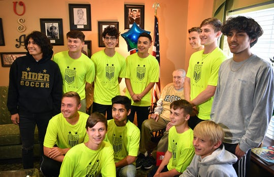 World War II veteran Joe Cuba takes a photo with the Rider High School soccer team Wednesday after they delivered cards, flowers, a cake and balloons for his upcoming 100th birthday on Saturday. Cuba's family requested on social media for him to receive 100 cards for his 100th birthday and he's received approximately 16,000.
