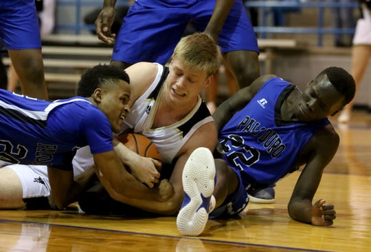 Rider's Ben Moffat fights for the ball by Palo Duro's Mohammed Musa, left, and Akuel Kot (22) in the Region I-5A regional quarterfinal Tuesday, Feb. 26, 2019, in Childress.