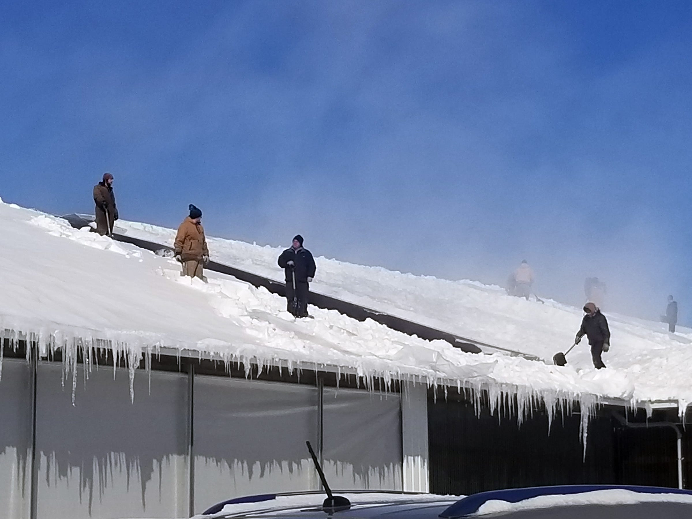 Volunteers help remove snow off a barn roof at Dutch Dairy in Thorp.