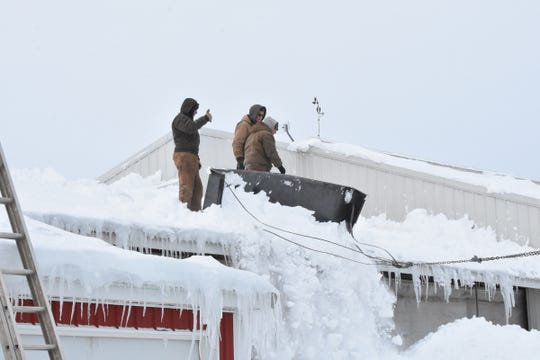 Volunteers work to scrape snow off a barn roof at Dutch Dairy in Thorp.