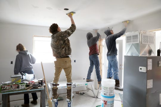 A group of students in Mid-East's carpentry program work on drywall in a house the program is building for Habitat for Humanity.