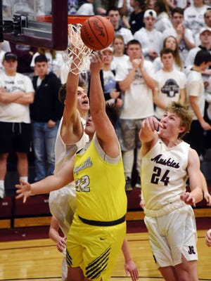 John Glenn's Devin Burris, left, and Reece Perkins try to block the shot of Maysville's Ethyn McClelland during a Division II sectional game in New Concord. John Glenn won, 54-40, to improve to 19-4.