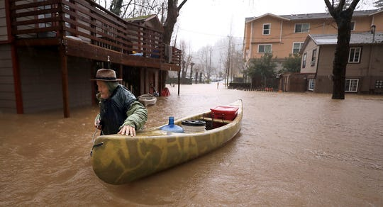 Sycamore Court resident Jesse Hagan evacuates to higher ground in the apartment complex in lower Guerneville, California, on Feb. 26, 2019.