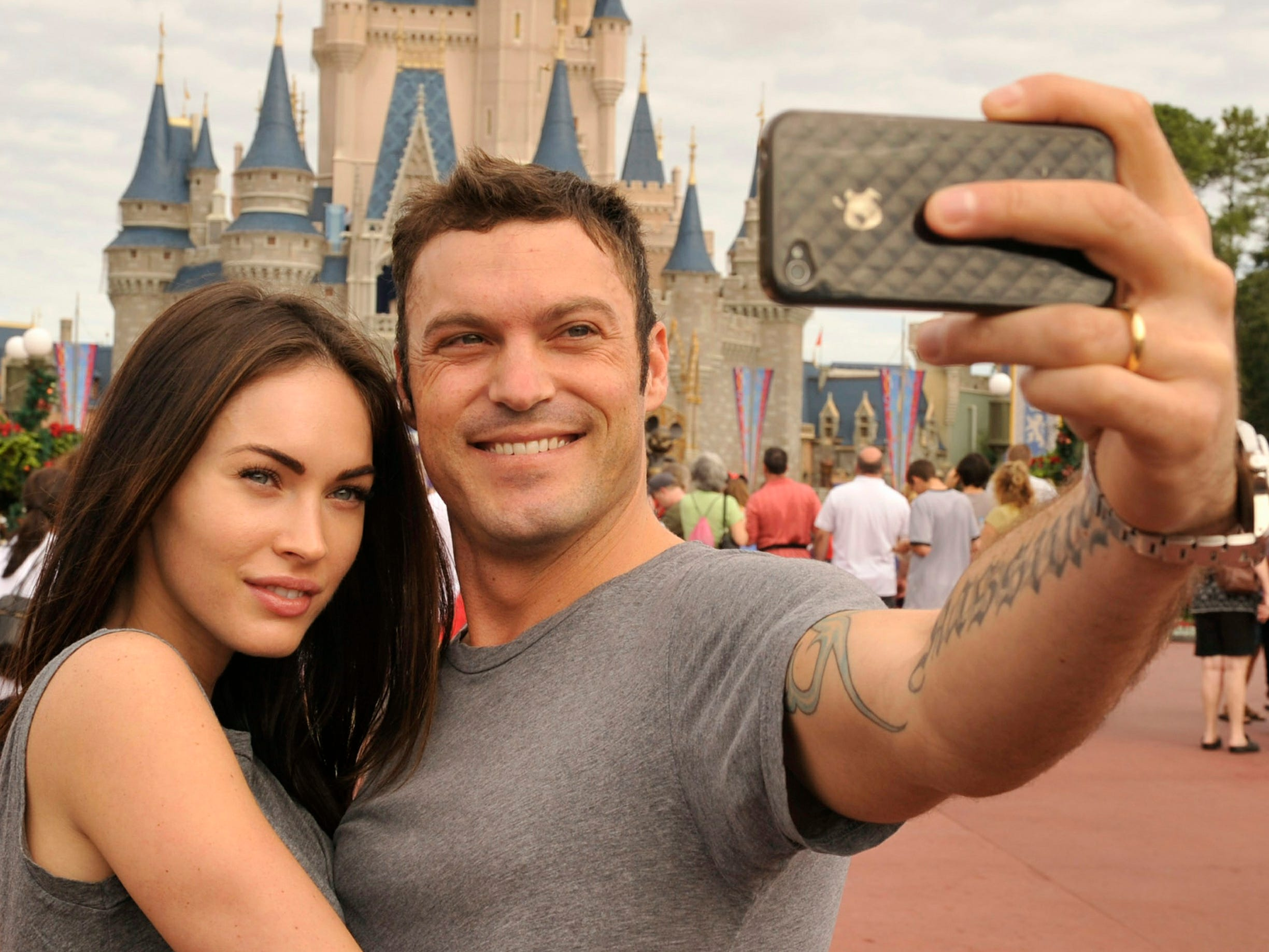 """ORG XMIT: 106794661 LAKE BUENA VISTA, FL - NOVEMBER 26:  In this handout photo provided by Disney, actor Brian Austin Green (right) and his wife, actress/model Megan Fox (left), take a souvenir photo in the Magic Kingdom November 26, 2010 in Lake Buena Vista, Florida.  Green (""""Beverly Hills, 90210"""", """"Desperate Housewives"""") and Fox (""""Transformers,"""" """"Transformers: Revenge of the Fallen"""") were married in June 2010 in Hawaii.  (Photo by Gene Duncan/Disney via Getty Images) ORIG FILE ID: HUSBAND/WIFE BRIAN AUSTIN GREEN AND MEGAN FOX AT WALT DISNEY WOR"""