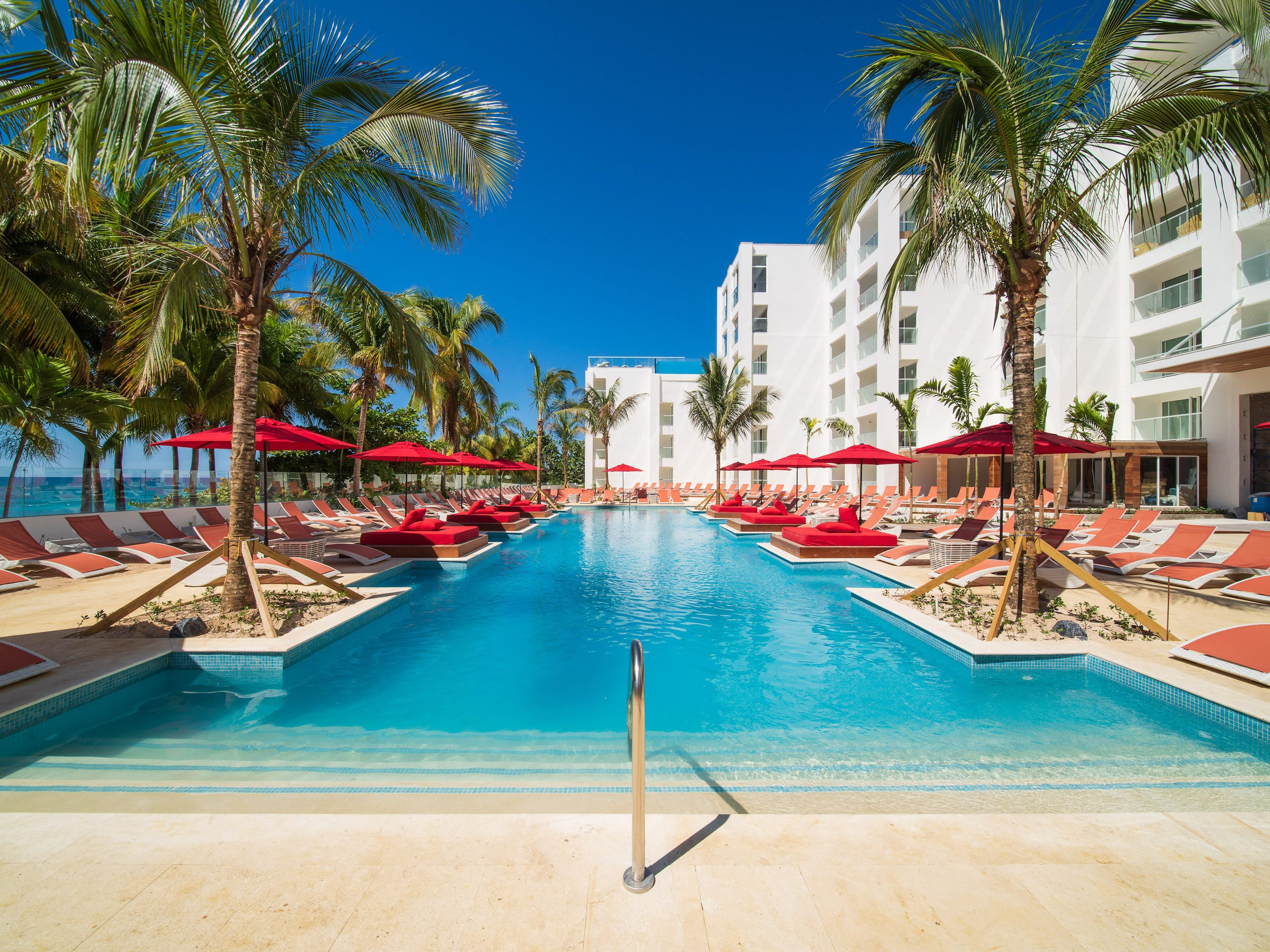 The S Hotel Jamaica's beachfront main pool with swim-out cabanas is pretty in blues and reds.