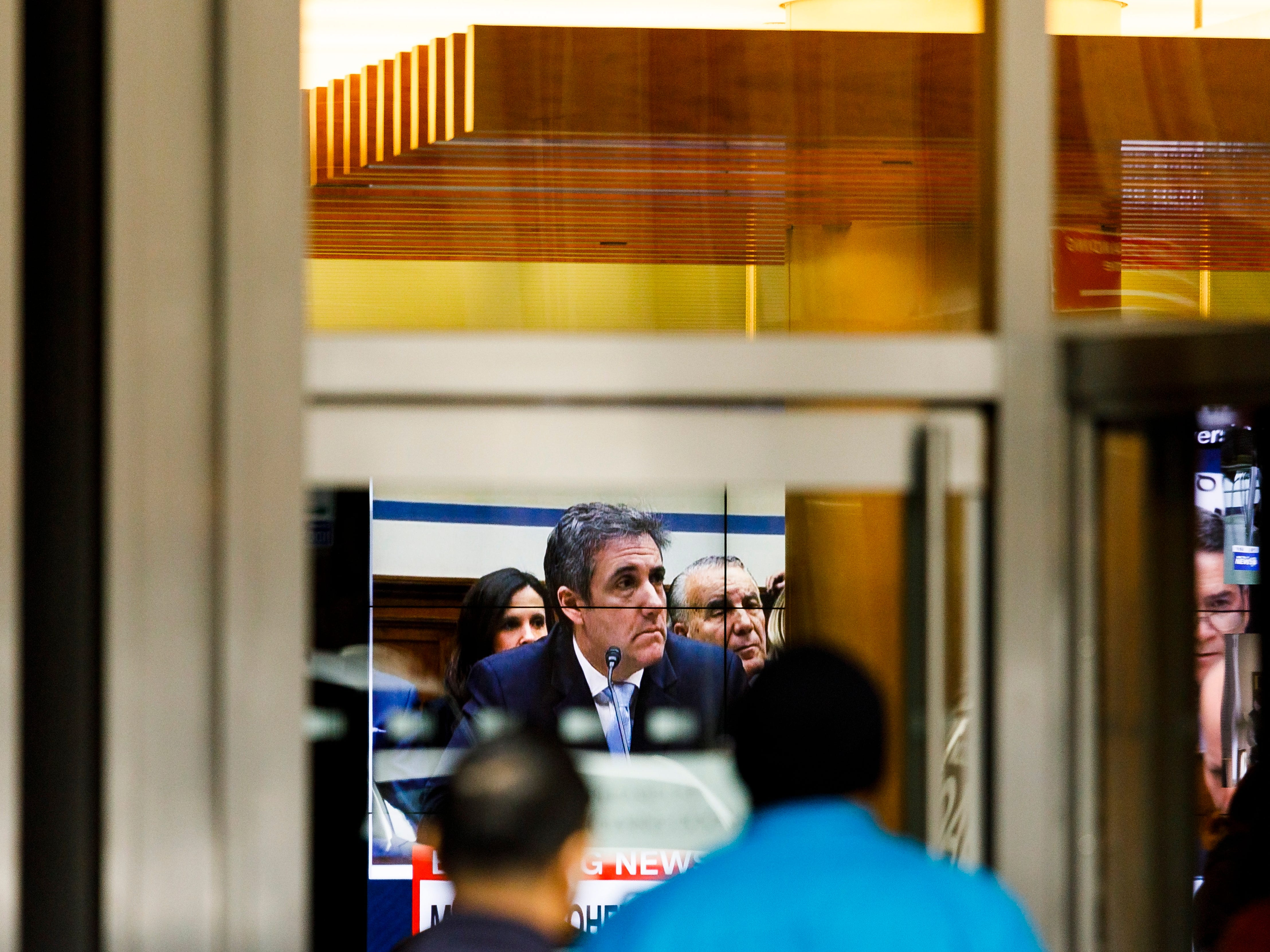 People watch Michael Cohen, President Donald Trump's former personal attorney, testifies before a congressional committee on a television in a building lobby in New York.
