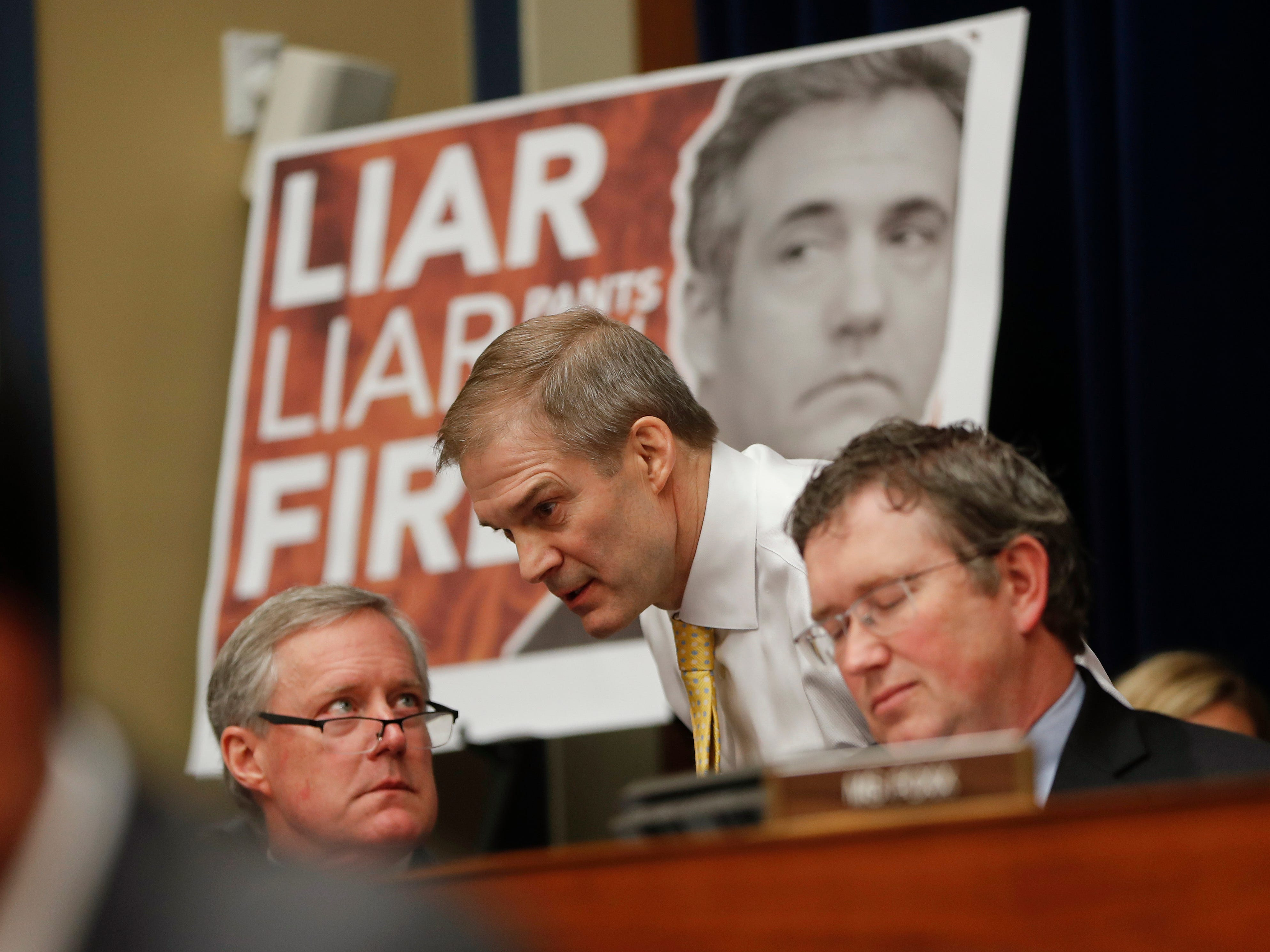 Rep. Jim Jordan, R-Ohio, center, ranking member of the Committee on Oversight and Reform talks with Rep. Mark Meadows, R-N.C., left, and Rep. Thomas Massie, R-Ky., right, during testimony by Michael Cohen, President Donald Trump's former personal lawyer on Capitol Hill.