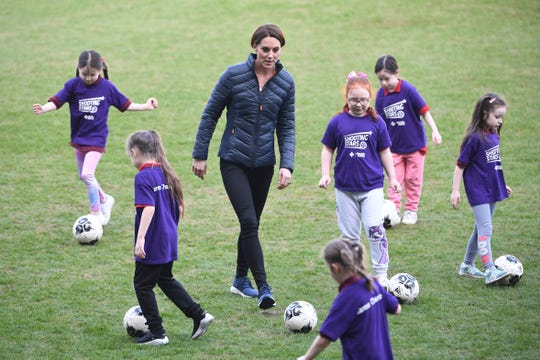c5737604b5a70 Duchess Kate plays football with children during a visit to the Irish  Football Association in Belfast