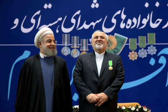 "In this Feb. 8, 2016 file photo, Iranian President Hassan Rouhani, left, and his Foreign Minister Mohammad Javad Zarif pose for a photograph after Zarif was awarded a ""Medal of Merit"" in a ceremony in Tehran, Iran."