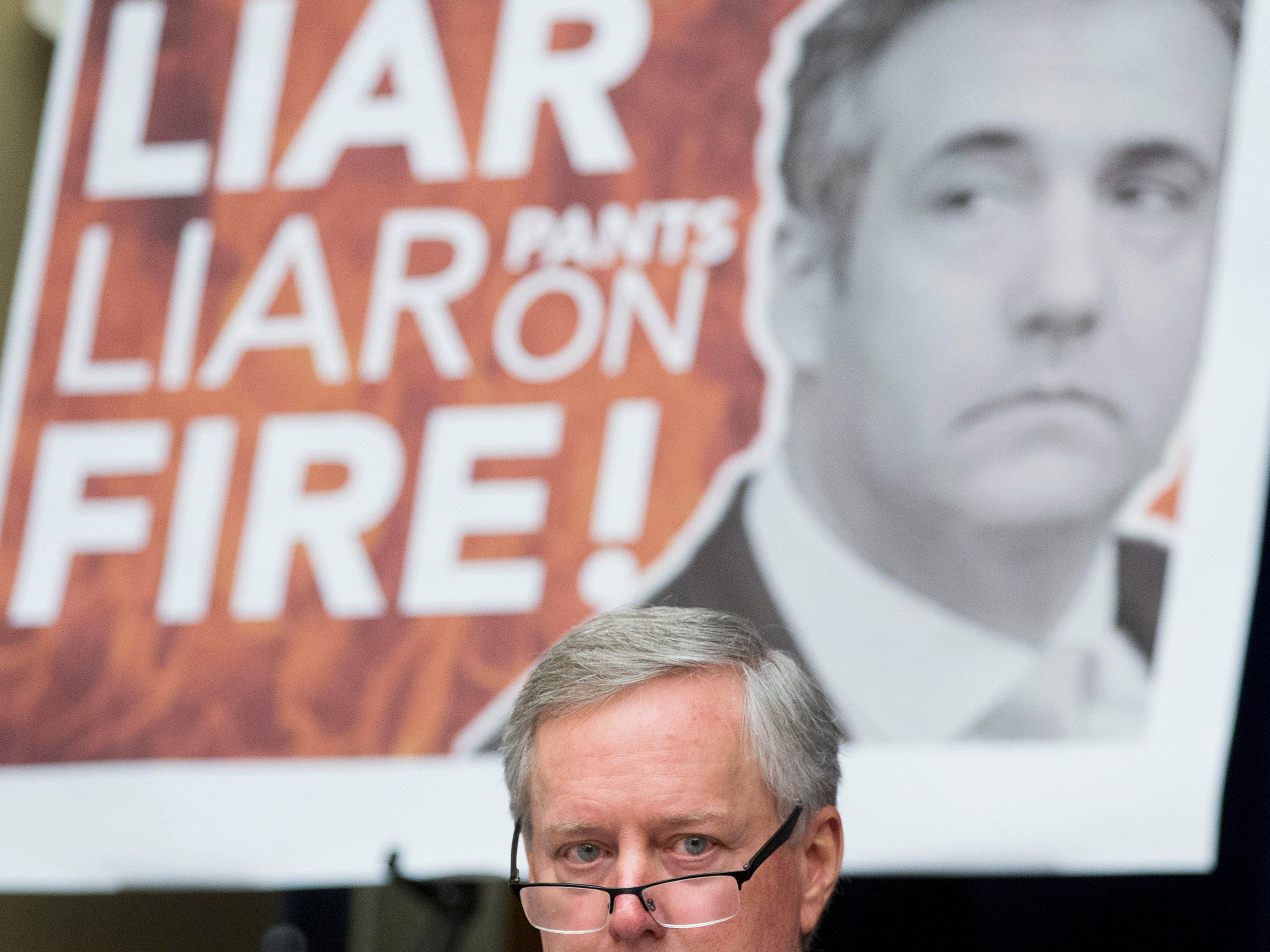 A sign depicts Michael Cohen, former attorney to President Donald Trump, behind Rep. Mark Meadows, R-N.C. during Cohen's testimony before the House Oversight and Reform Committee.