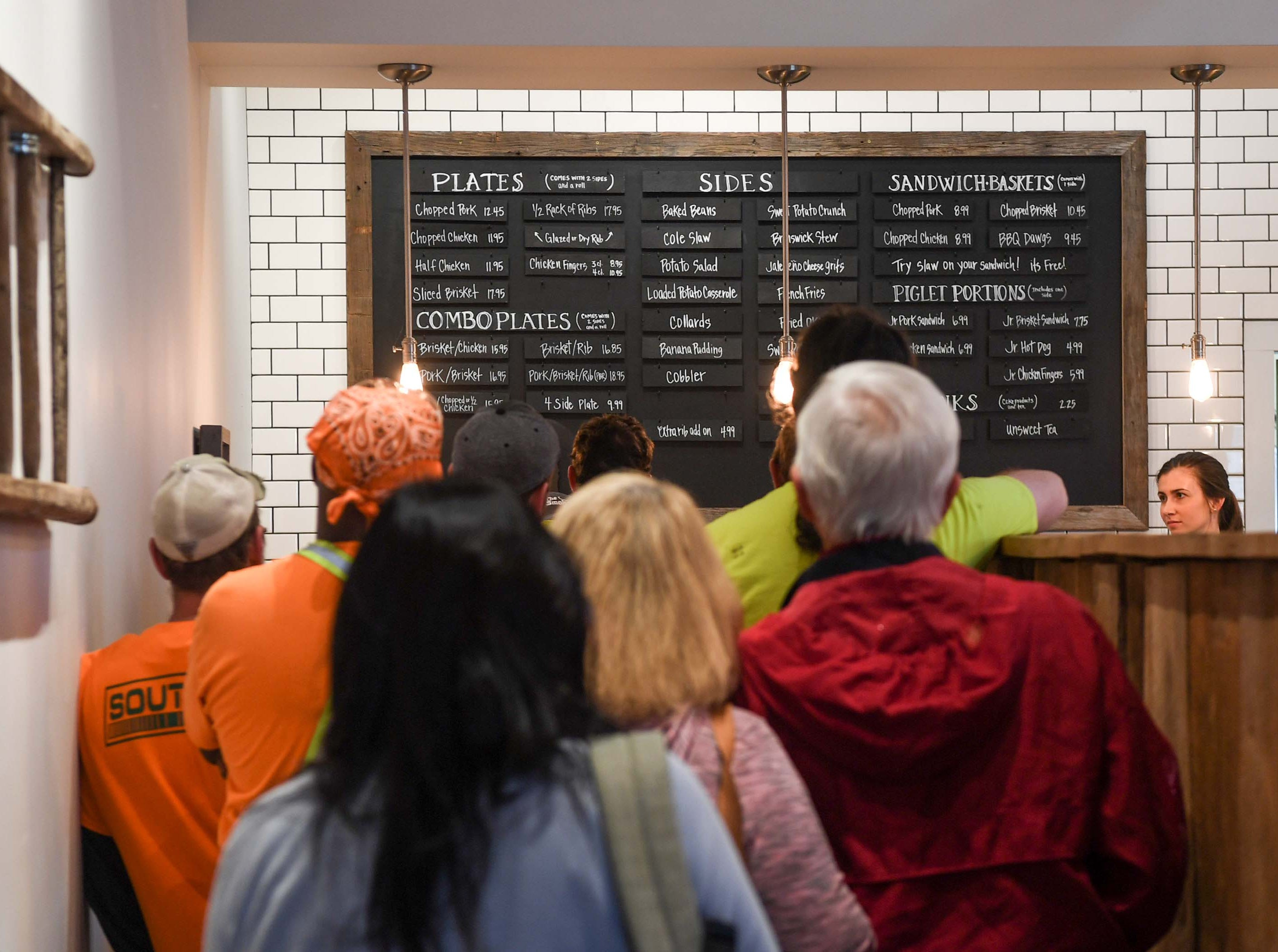 The first group of customers line up on opening day of Smokin' Pig on Evergreen Road in Anderson, order their lunch Thursday, February 28, 2019. The new location is the fourth, with locations in Pendleton, Williamston, and Easley.