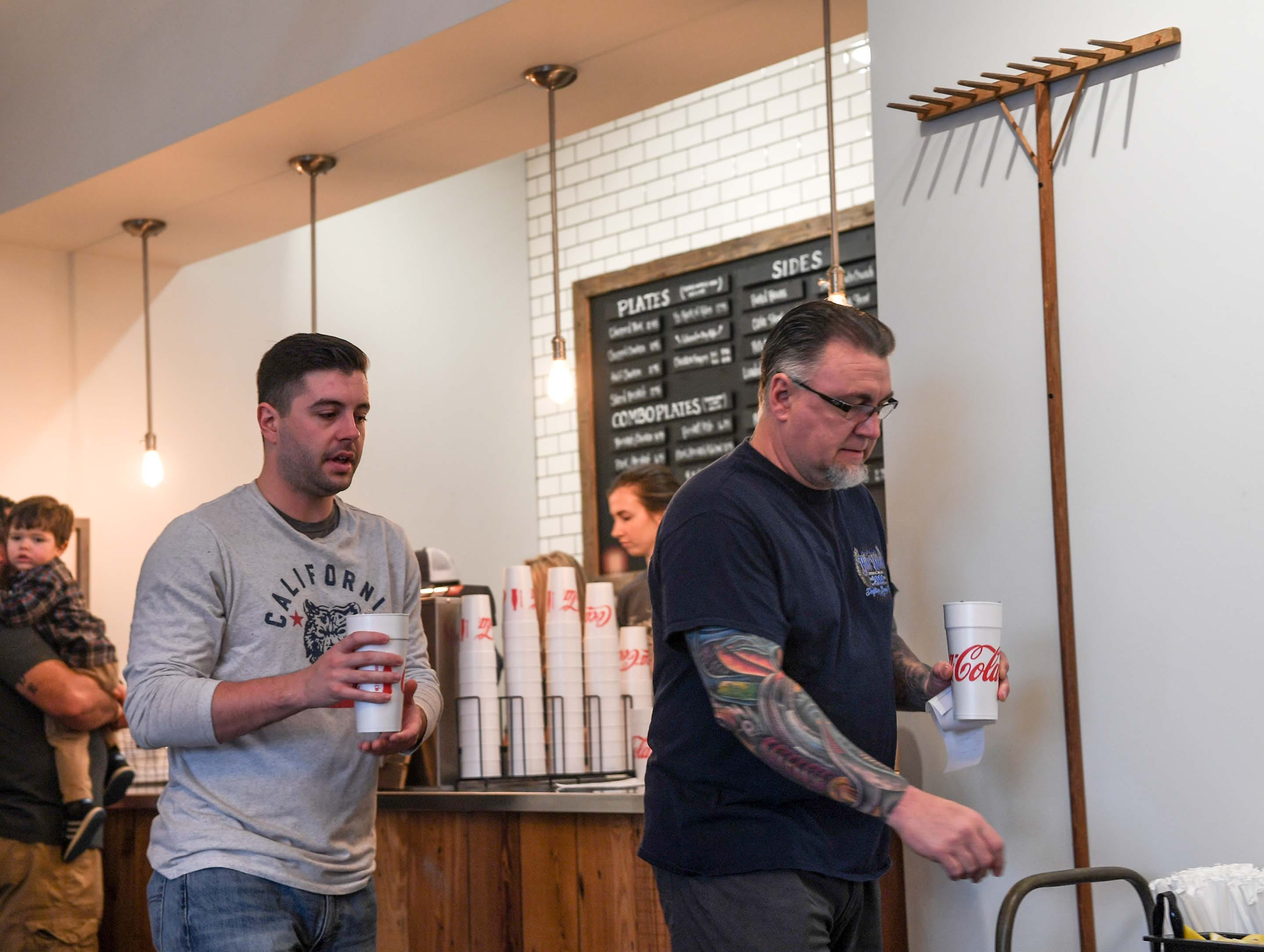Steele Ramey, left, and his father Scott Ramey of Anderson the first in line on opening day of Smokin' Pig on Evergreen Road in Anderson, move along after ordering their lunch Thursday, February 28, 2019. The new location is the fourth, with locations in Pendleton, Williamston, and Easley.