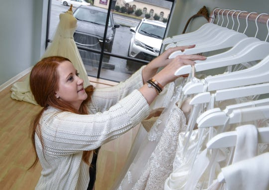 Allie Walker looks at some of the 38 dresses at her business, Katherine Marie Bridal Boutique, on East Greenville Street in Anderson Thursday, February 28, 2019. Walker is at the location next to the Bagel Shop until her downtown Anderson location is renovated at 106 East Benson Street, previously the Anderson School of Dance.