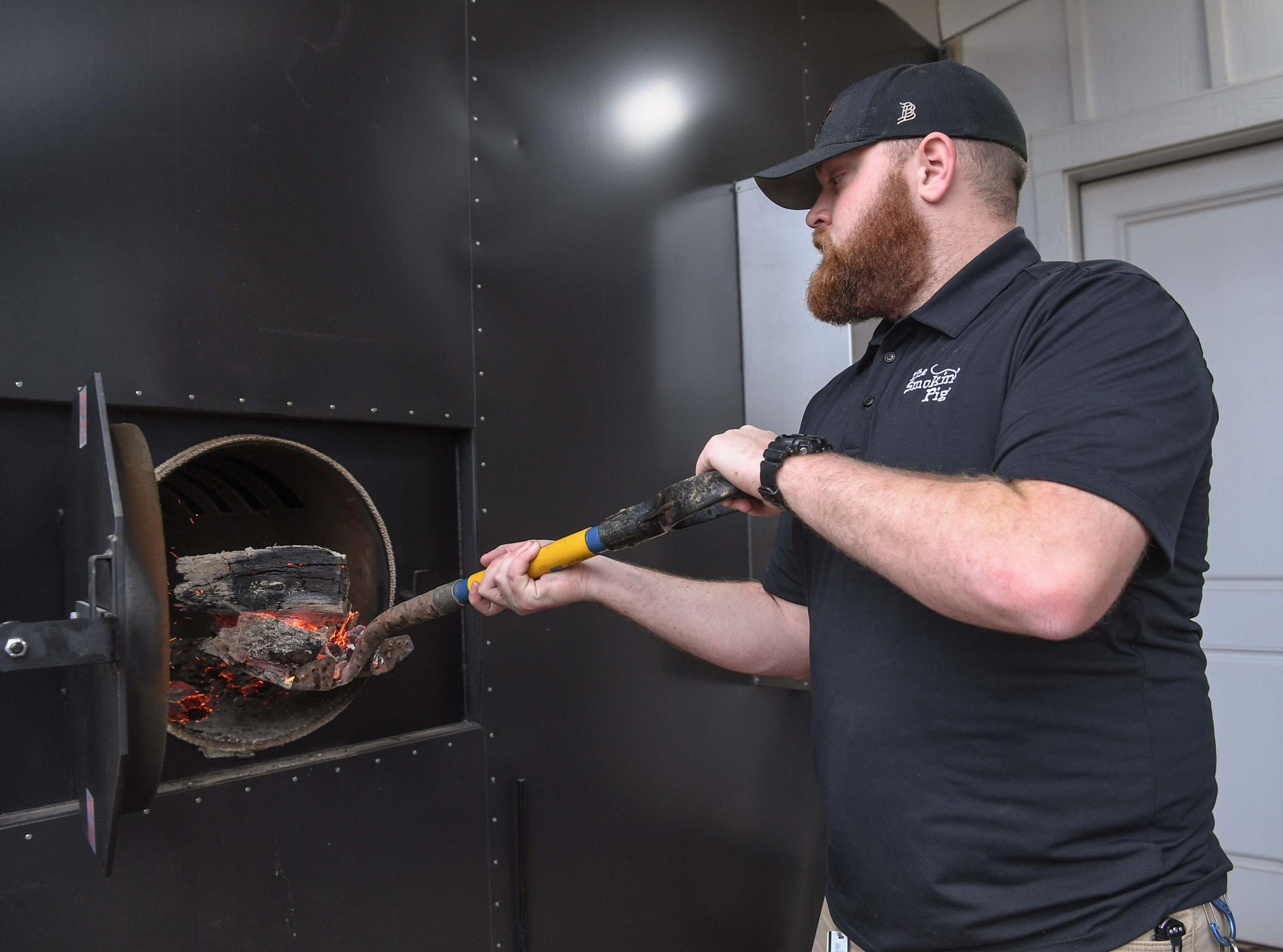 Chris McCroskey checks on the firewood in the smoker cooking brisket at The Smokin' Pig on Evergreen Road in Anderson. The new location opened February 28, 2019, one of four locations including Pendleton, Williamston, and Easley.