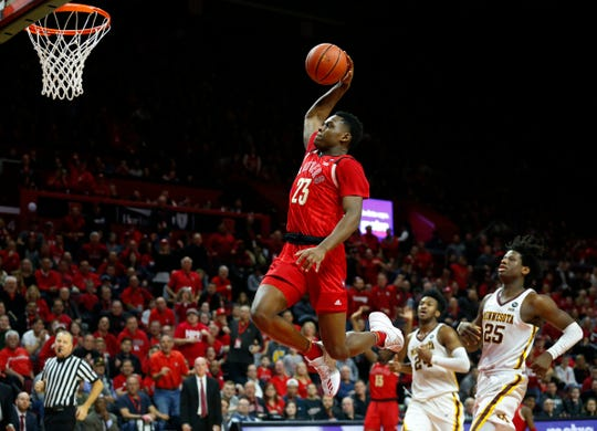 Rutgers Scarlet Knights guard Montez Mathis (23) dunks against Minnesota Golden Gophers forward Eric Curry (24) and center Daniel Oturu (25)