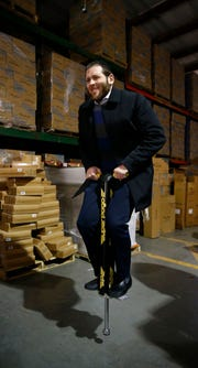 Flybar President & CEO Saul Wolhendler takes a bounce on the 'Super Pogo' at the company's Howell Township warehouse Wednesday, February 27, 2019.   Flybar is the original pogo stick company and has moved its operations to the township.