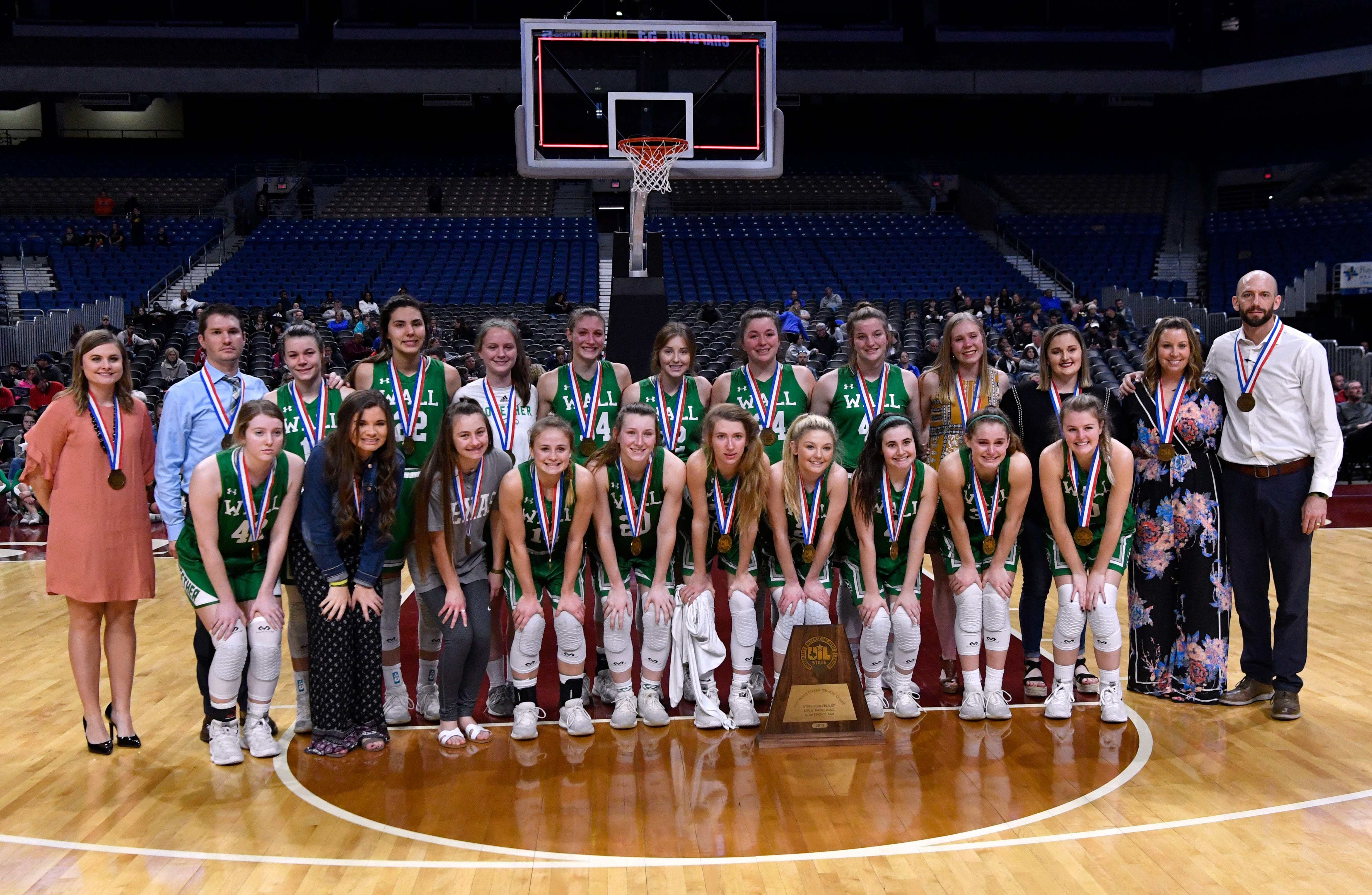 The Wall Lady Hawks pose for a team portrait with the State Semi-finalist girls basketball Class 3A trophy at the Alamodome in San Antonio Thursday Feb. 28, 2019.