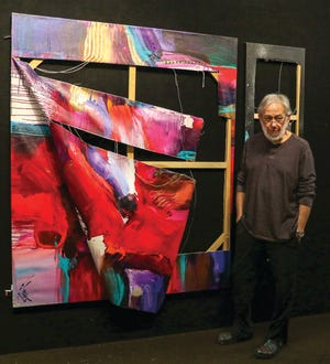 Jonas Gerard stands next to one of his paintings that was vandalized while displayed at Asheville Regional Airport. The Asheville artist has been targeted through more than 20 acts of vandalism over the past year amid sexual misconduct allegations against him. Gerard denies the accusations.