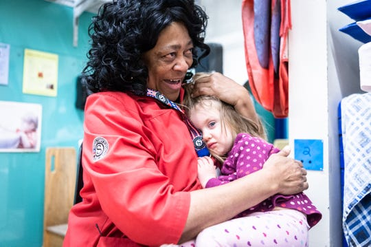 Thomasina Brownlee, 63, one of 55 foster grandparents working with the Land of Sky Regional Council, which offers the federally-funded Foster Grandparents program, embraces Selah Sturtevant-Gilliam, 2 1/2, at the Asheville YWCA's Early Learning Program, on Jan. 16, 2019, where she has worked five days a week for the past six years.