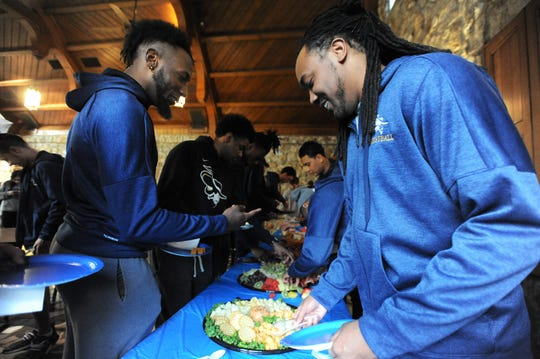Montreat College basketball players, including senior Alonzo Mobley, left, serve themselves during a gathering on Feb. 27, when the Cavs learned they would be a number 5 seed in the NAIA Division II Men's Basketball National Championship Tournament in Sioux Falls, South Dakota.