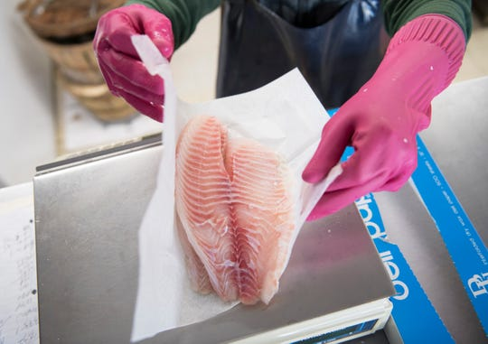 Justin Gang, owner of Fisher's Seafood in Willingboro,  weighs tilapia for a customer on Thursday, February 21, 2019.