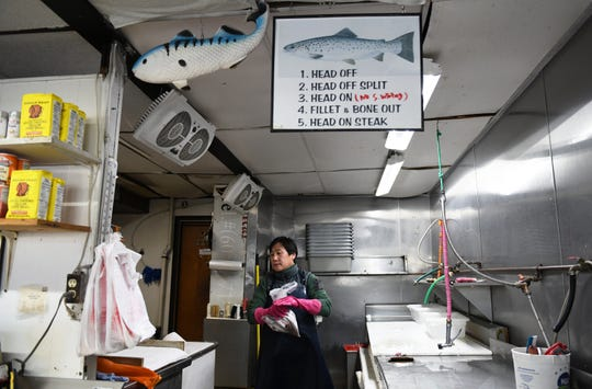 Justin Gang, owner of Fisher's Seafoodin Willingboro,  bags small whiting for a customer on Thursday, February 21, 2019.