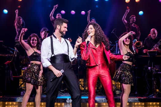 "Mauricio Martinez (L) as Emilio Estefan and Christie Prades as Gloria Estefan perform with the company of ""On Your Feet!"" The show, built around the Cuban-fusion pop music the couple made famous, runs March 19-24 at the Aronoff Center as part of the Broadway Series."