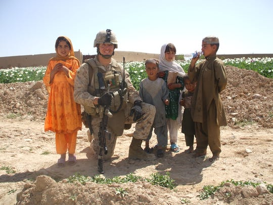 Matthew Peterson, an Iowa native and Marine, talks with the children of a poppy farmer who had decided to work with the U.S. military in  Sangin, Afghanistan, in January 2011.