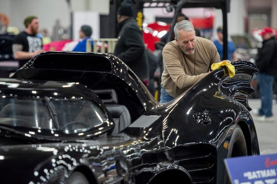 """John Davidson, of Louisville, KY., polishes the Batmobile movie prop from the movie """"Batman Returns"""", owned by Carl Casper during set up day for the Autorama custom vehicle show at Cobo Center, in Detroit, February 28, 2019."""
