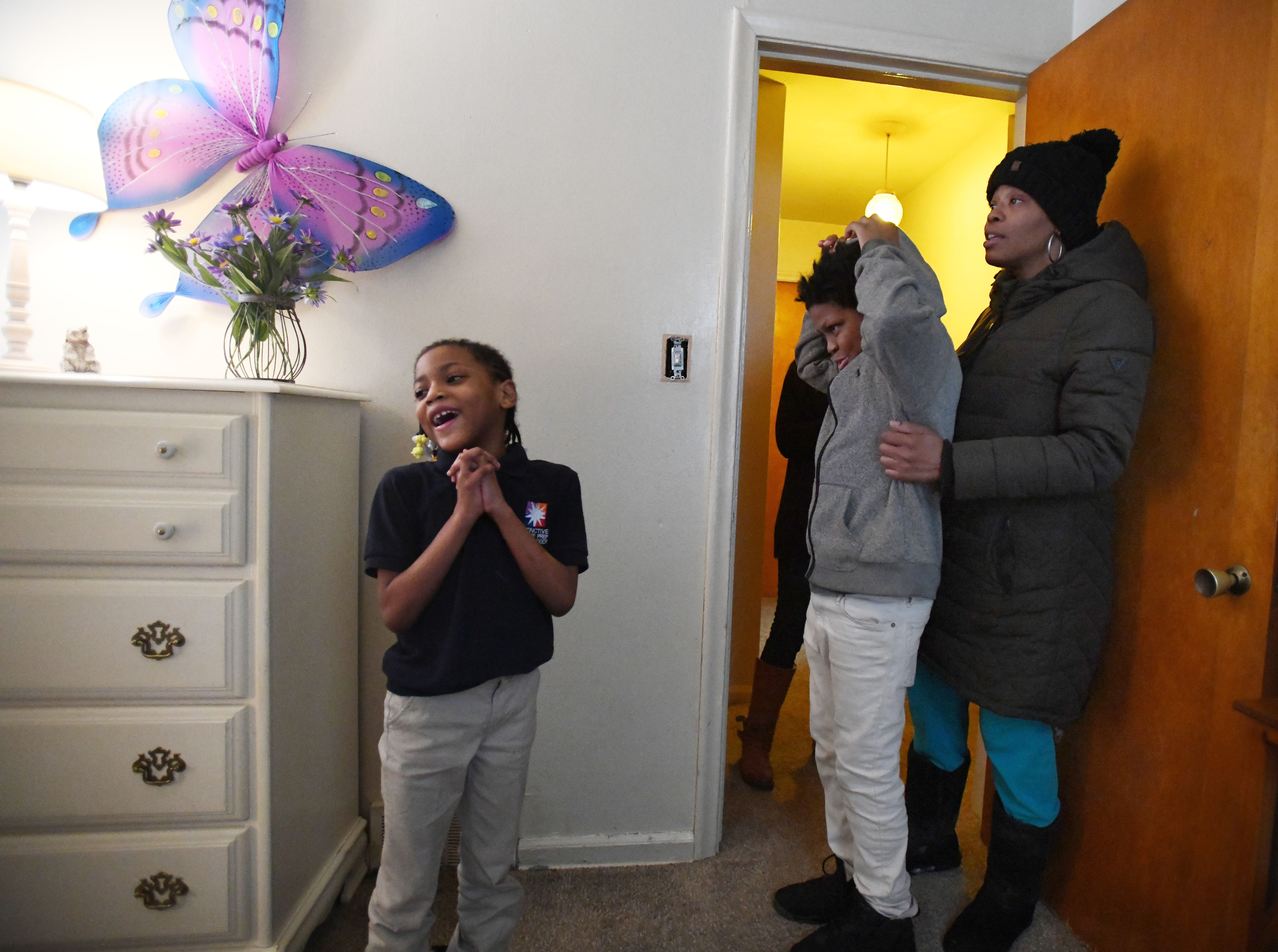 Ja'Kayla, 7, is overwhelmed by her beautiful pink and purple room as her  brother Jai'Vonte, 12, and mother Jamiliah Powers-McCoy stand in the doorway.